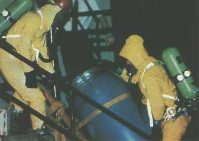 塩酸入りの樽を運び出す捜査員