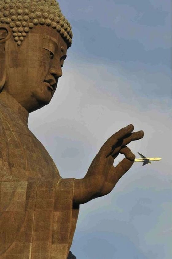 A statue of Buddha captures a commercial airliner by its tail