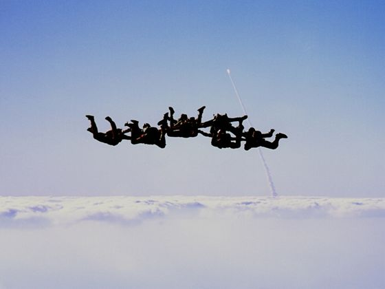 Space shuttle Discovery being launched into orbit as skydivers descend