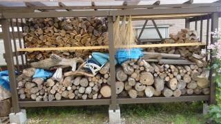 割ってない玉が積まれた薪棚