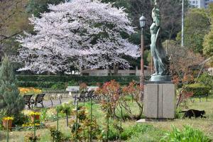 満開の桜、女神像、立ち去る黒い猫