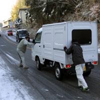 冬の坂道で滑る車