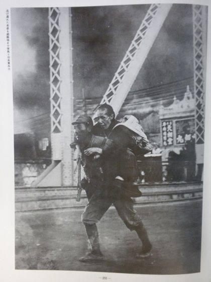 支那軍に町を焼かれ、逃げ遅れた老婆を避難地まで背負う日本軍兵士 『写真集支那事変』